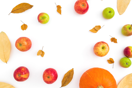 Autumn frame with fall dried leaves, apples and pumpkin on white background. Flat lay, top view