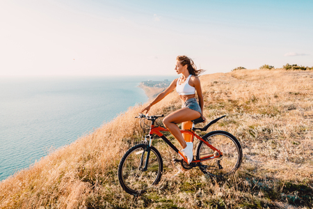 Young pretty woman with mountain bicycle in white shirt, shorts and white sneakers