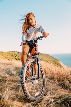 Young active woman with mountain bicycle in outdoor