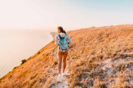 Attractive sporty woman in nature at warm sunset. Happy girl on a walk in the mountains Stock Photo