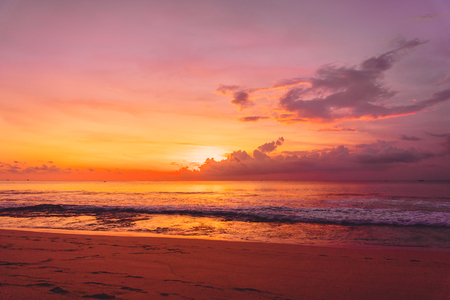 Colorful bright sunset or sunrise at sandy beach with ocean in California