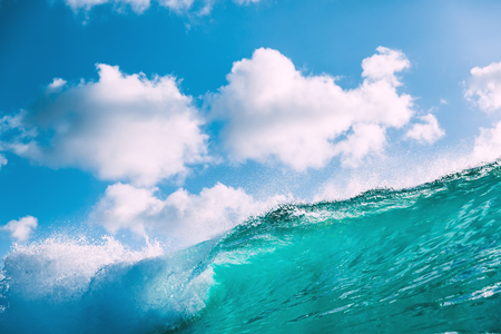 Breaking blue wave with sunlight and sky with clouds. Stock Photo