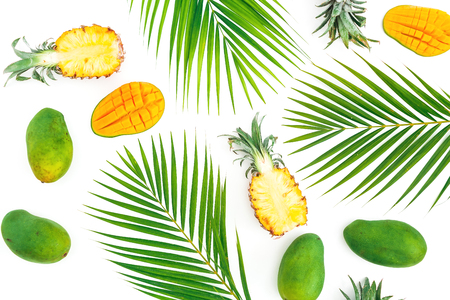 Tropical pattern of pineapple and mango fruits with palm leaves on white background. Flat lay, top view.