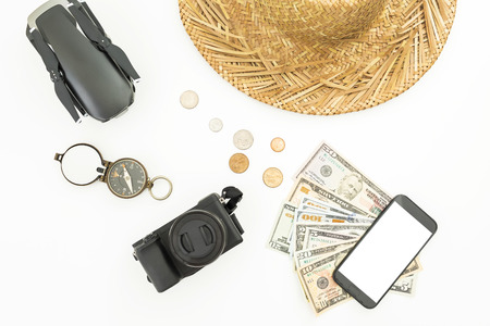 Travel concept. Drone, straw hat, photo camera, compass and usa cash on white background. Flat lay, top view. Stock Photo