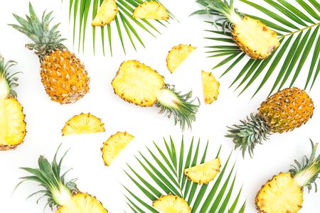 Tropical food pattern made of pineapple fruits with palm leaves on white background. Flat lay, top view. Stock Photo