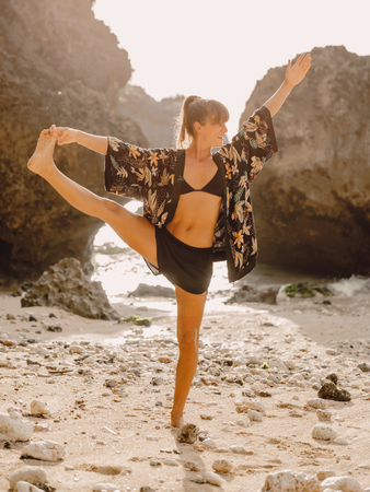 Beautiful yoga woman at beach with sunset light.