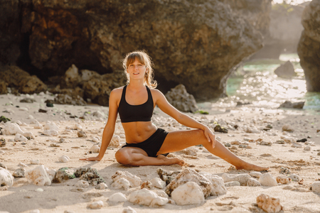 Sporty woman at the ocean beach. Yoga with sunset light