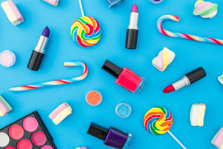 Background with female cosmetics and bright candy on a blue background. Top view. Flat lay. Creativity beauty desk.