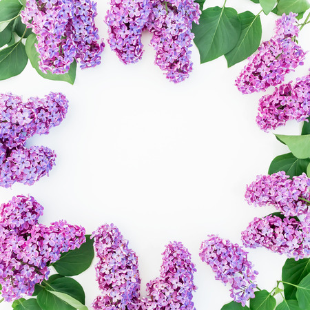 Floral round frame with purple flowers and leaves on white background. Flat lay, top view