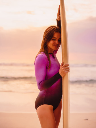 Beautiful surfer girl with surfboard at sunset
