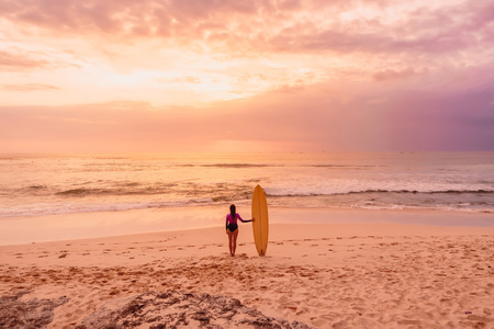 Surf girl with old school surfboard at beach. Surfer woman with sunset or sunrise colors. Stock Photo