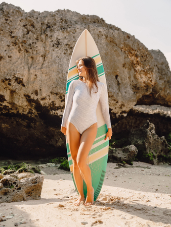 Young surf girl with surfboard poising at beach. Surfer woman standing at beach.