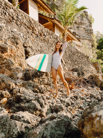 Happy surfer woman with surfboard on a rocky shore