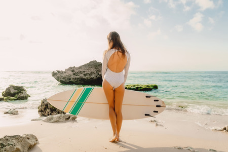 Beautiful sexy surfer girl on a sand beach Stock Photo