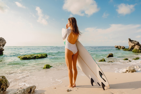 Surf girl with surfboard looking at ocean. Beautiful surfer woman at beach. Stock Photo