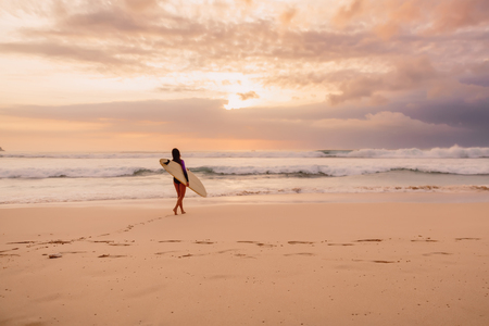 Surf girl go to ocean for surfing. Surfer woman on the beach at sunset Stock Photo