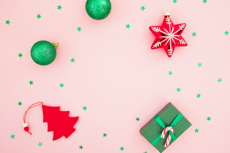 Christmas composition. Christmas gift box, toys and glittering confetti on pink background. Flat lay, top view.