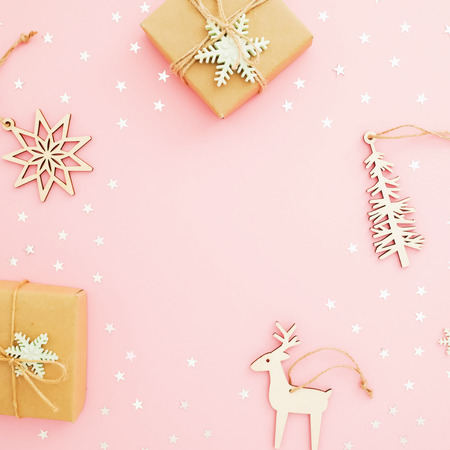 Christmas composition. Christmas gift box, confetti on pink background. Flat lay, top view.