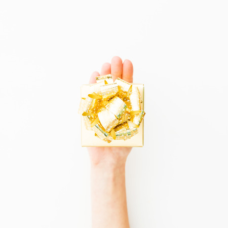 Woman holding golden gift box on white background. Happy moment