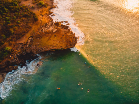 Aerial view of a rocky shore with surfers, waves and warm sunset. Drone shot in bali