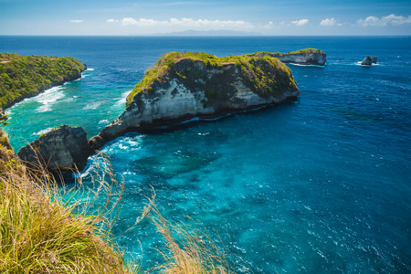 Rocky islands in Nusa Penida, Bali, Indonesia. Blue sky and turquoise Water.