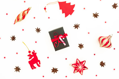 Christmas pattern. Christmas gift box, red toys and glittering confetti on white background. Flat lay, top view. Stock Photo