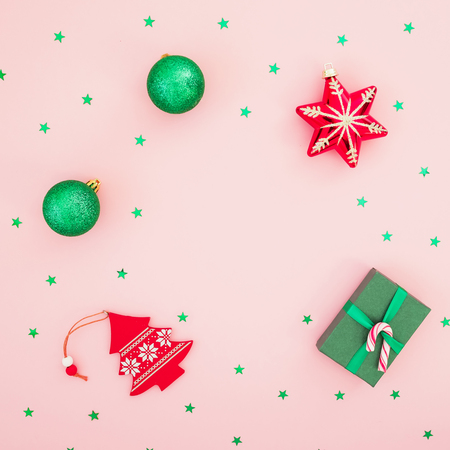 Christmas composition. Gift box, toys and glittering green confetti on pink background. Flat lay, top view.