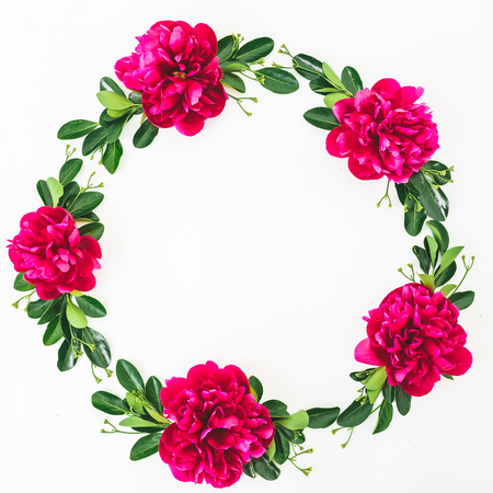 Round frame of red flowers and leaves on white background. Flat lay, top view.