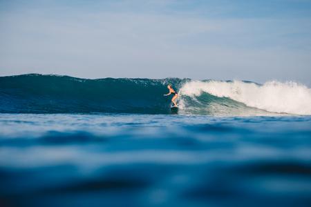 La giovane ragazza del surfista cavalca sull'onda dell'oceano perfetta.
