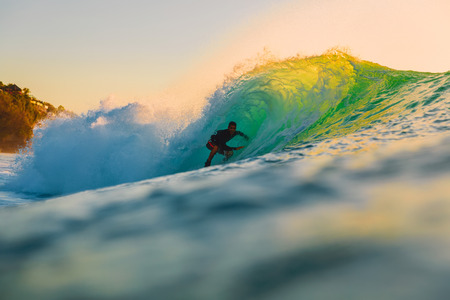 September 8, 2018. Bali, Indonesia. Surfer ride on barrel wave at sunset. Professional surfing in the ocean, Bingin beach Editorial