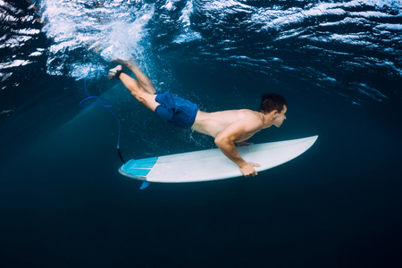 Professional surfer with surfboard dive underwater with ocean wave.