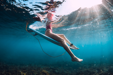 Attractive surfer girl sit at surfboard underwater in ocean