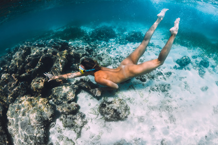 Beautiful woman swimming and dive in tropical ocean. Underwater photo with woman near coral reef