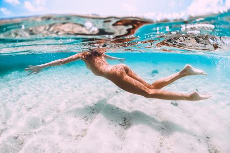 Mujer joven delgada nadando en el océano tropical, foto submarina Foto de archivo
