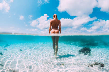 Beautiful naked woman in tropical ocean, underwater fifty fifty photo. Bahamas island