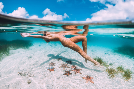 Beautiful woman floating and relax in tropical ocean with starfish, underwater photo Reklamní fotografie - 112457791