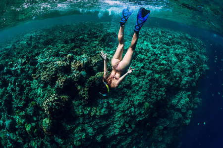 Woman free diver dive in the tropical ocean