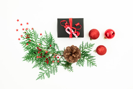 Merry Christmas composition with fir branches, black gift box and red balls with confetti on white background. Festive background. Flat lay, top view