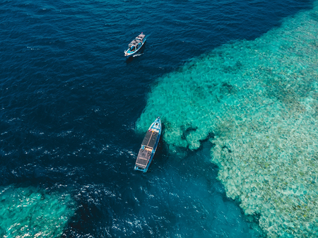 Tour boats in blue ocean on Menjangan island. Aerial view. Stock Photo