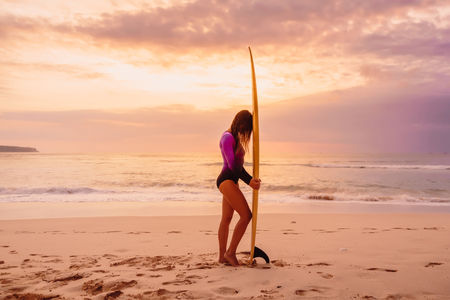 Surfer girl posing with surfboard on a beach at sunset
