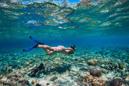 Woman free diver in bikini swimming underwater in the tropical blue ocean Stock Photo