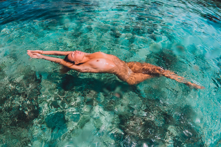 Beautiful woman floating and relax in tropical ocean Standard-Bild