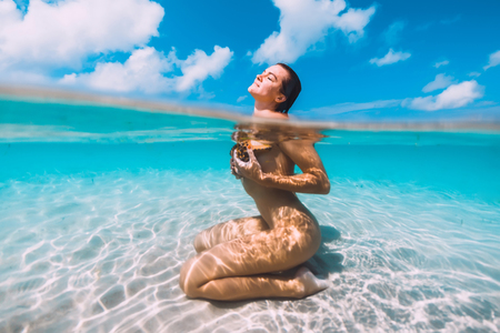 Woman relax in blue ocean with starfish, underwater in tropical sea Stockfoto