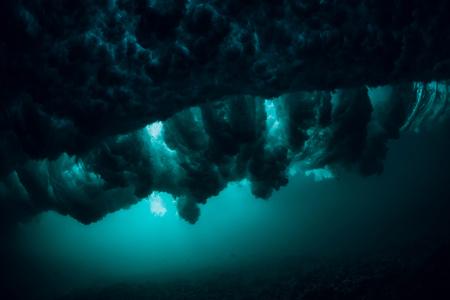 Wave underwater with air bubbles. Stormy ocean in underwater