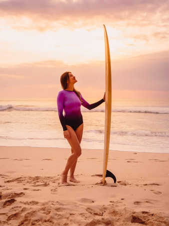 Surfer girl posing with surfboard on the beach at sunset