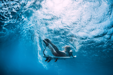 Attractive surfer girl dive underwater with under wave. Banque d'images - 117598407