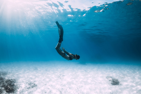 Woman freediver glides over sandy sea with fins. Freediving in blue ocean
