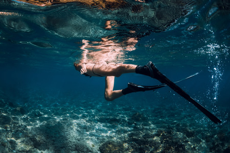 Woman freediver with fins and corals. Freediving underwater in blue ocean Stock Photo