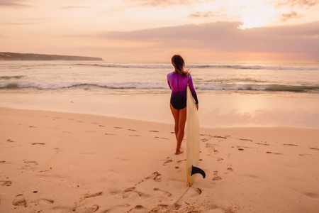 Surfer girl with surfboard on a beach at sunset or sunrise.