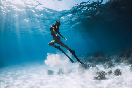 Woman freediver with fins swim over sandy bottom and sun rays underwater ocean